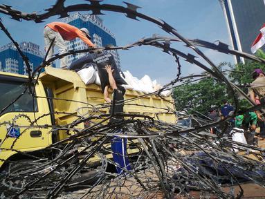 Petugas tampak mengangkut tanaman yang rusak di Taman Silang Monas, Jakarta, Jumat (22/8/14). (Liputan6.com/Faizal Fanani)