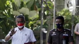Ketua DPRD DKI Jakarta Prasetyo Edi Marsudi (kiri) melambaikan tangan saat tiba di halaman Gedung Komisi Pemberantasan Korupsi (KPK), Jakarta, Selasa (21/9/2021). Prasetyo akan menjalani pemeriksaan dalam kasus dugaan korupsi pengadaan lahan di Munjul pada tahun 2019. (Liputan6.com/Angga Yuniar)
