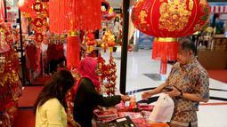 Pengunjung membeli pernak-pernik Imlek di atrium Lippo Mall Puri, Jakarta, Jumat (01/2). Kegiatan menyambut Tahun Baru Imlek yang mengusung tema Let's Gong Xi berlangsung hingga 28 Februari 2019. (Liputan6.com/Fery Pradolo)