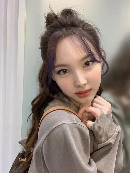 Nayeon mewarnai rambut panjangnya menjadi cokelat. Menariknya, poninya diwarnai dengan ungu. Gaya rambut ponytail setengah rambut yang acak.Instagram @twicetagram