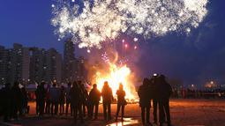 """Peserta menyaksikan kembang api menjelang perayaan """"Jeongwol Daeboreum"""" di Seoul, Korea Selatan (1/3). Jeongwol Daeboreum merupakan perayaan hari libur tradisional Korea untuk merayakan bulan purnama pertama kalender lunar. (AFP Photo/Jung Yeon-je)"""