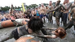Turis mengikuti permainan dalam Festival lumpur Boryeong di Daecheon, Boryeong, Korea Selatan, (22/7). Festival yang berlangsung 21-30 Juli bertujuan untuk mendorong penggunaan lumpur sebagai kosmetik untuk perawatan kulit. (AP Photo/Ahn Young-joon)