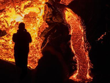 Seseorang menyaksikan aliran lahar dari letusan gunung berapi di Semenanjung Reykjanes, barat daya Islandia, Senin (29/3/2021). Letusan gunung berapi tersebut masih menarik ribuan orang yang berharap untuk mendekati aliran lahar. (AP Photo/Marco Di Marco)
