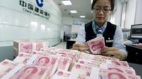 Petugas menghitung lembaran 100 yuan di cabang China Construction Bank di Hai'an, provinsi Jiangsu, 10 Agustus 2015. Langkah Bank Sentral China menurunkan nilai tukar yuan terhadap dolar AS langsung membuat pelaku pasar ketakutan. (REUTERS/China Daily)