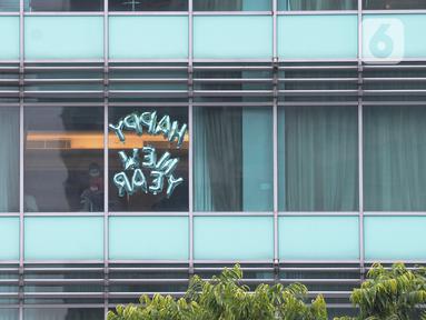 "Tamu berdiri di jendela salah satu kamar hotel yang dipasangi tulisan ""Happy New Year"" di Bundaran HI, Jakarta, Kamis (31/12/2020). Hotel menjadi alternatif bagi warga yang untuk merayakan pergantian malam Tahun Baru. (merdeka.com/Imam Buhori)"