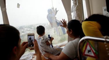 Petugas pembersih kaca berkostum Captain America mengejutkan pasien anak ketika turun dari atap rumah sakit anak-anak di Guadalupe, Meksiko, 30 April 2019. Mereka bergelantungan di luar jendela dengan mengenakan kostum superhero untuk menghibur anak- anak yang sedang sakit. (REUTERS/Daniel Becerril)
