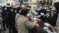 Warga menerima masker wajah gratis dalam sebuah toko kosmetik di Tsuen Wan, Hong Kong, Selasa (28/1/2020). Hong Kong terkonfirmasi memiliki delapan kasus infeksi virus corona. (AP Photo/Achmad Ibrahim)