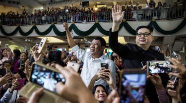Peniru Presiden Filipina Rodrigo Duterte, Cresencio Extreme (tengah) dan peniru pemimpin Korea Utara Kim Jong Un, Howard X melambaikan tangan ketika menghadiri kebaktian gereja di pusat Hong Kong pada 3 Februari 2019. (ISAAC LAWRENCE/AFP)