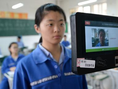 Salah satu peserta ujian melewati pemeriksaan menggunakan pendeteksi wajah selama simulasi di Handan, Provinsi Hebei, China, (6/6). Sebanyak 9,4 juta lulusan SMA China akan mengikuti ujian masuk perguruan tinggi atau Gaokao. (AFP/STR)