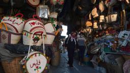 Perempuan Tunisa mengenakan masker untuk melindungi diri dari virus Corona mengunjungi sebuah pasar saat kasus baru infeksi melonjak, di kota Gabes, Rabu (27/8/2020). Tunisia pada 25 Agustus 2020 melaporkan peningkatan tertinggi kasus baru Covid-19 dibandingkan minggu sebelumnya. (FETHI BELAID/AFP)