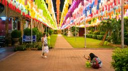 Orang-orang berfoto bersama lampion di Wat Phra That Hariphunchai, Lamphun, Thailand, 1 November 2020. Sekitar 100.000 lampion digantung di Wat Phra That Hariphunchai sebagai bagian dari perayaan festival tradisional Yi Peng. (Xinhua/Zhang Keren)