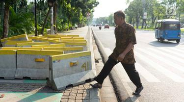 Pejalan kaki menghindari pembatas jalan yang menutupi trotoar di Jalan Medan Merdeka Utara, Jakarta, Rabu (3/7/2019). Pembatas jalan yang berada tidak pada tempatnya tersebut mengganggu pejalan kaki karena menutupi badan trotoar. (Liputan6.com/Immanuel Antonius)