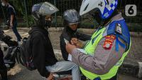 Petugas kepolisian lalu lintas saat menilang pengendara motor saat Operasi Zebra Jaya 2020 di kawasan Cawang, Jakarta, Senin (26/10/2020). Operasi Zebra Jaya dilaksanakan pada 26 Oktober-8 November 2020 untuk menekan jumlah pelanggaran lalu lintas. (Liputan6.com/Faizal Fanani)