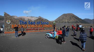 Wisatawan berswafoto di Tugu Rhe Sea of Sand Bromo Tengger Semeru National Park, Probolinggo, Jawa Timur, Minggu (8/7). Gunung Bromo masih menjadi destinasi wisata primadona yang ramai dikunjungi wisatawan setiap tahunnya. (Liputan6.com/Arya Manggala)