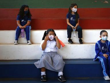 Siswa kelas satu mengenakan masker dan menjaga jarak saat kelas olahraga di sekolah teknik San Juan Bautista, Lambare, Paraguay, Rabu (17/2/2021). Beberapa SD swasta di Paraguay membuka kelas tatap muka minggu ini dengan protokol kesehatan ketat di tengah pandemi COVID-19. (AP Photo/Jorge Saenz)