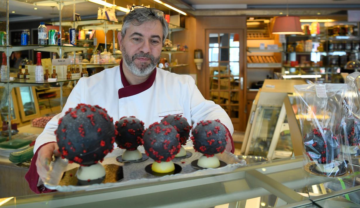 Pembuat cokelat, Jean-François Pre menunjukkan telur paskah berbentuk seperti Virus Corona di tokonya di Landivisiau, Prancis, 7 Maret 2020. Cokelat ini terbuat dari cokelat putih yang diberikan pewarna hitam serta dipadukan dengan kacang almond yang diwarnai merah. (Damien MEYER/AFP)