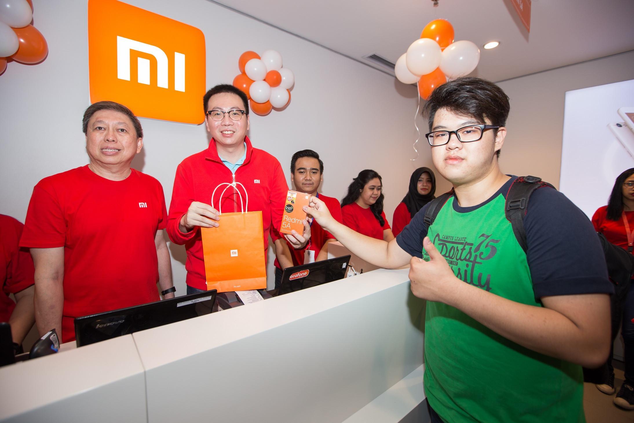 Head of Xiaomi South Pacific Region Steven Shi and Xiaomi Indonesia Country Manager (kiri) bersama Hasan Aula, CEO Erajaya Group melayani beberapa pelanggan pertama yang hadir pada pembukaan Mi Store MKG (Foto: Dok Xiaomi Indonesia)