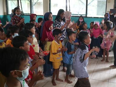 Direktur PAUD Institute Danang Sasongko (kiri) dan karyawan Askrindo menghibur anak-anak korban banjir dengan bermain, bernyanyi dan menari bersama di Kantor Kecamatan Cilamaya Wetan, Cikampek Jumat (12/02/2021). (Liputan6.com/Pool/Askrindo)