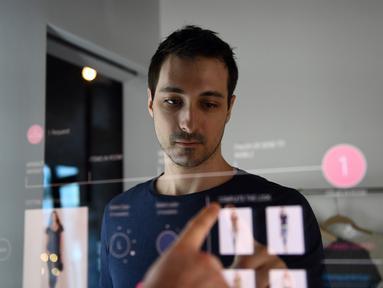 Peneliti Oak Labs, Wesley Bliss saat menggunakan cermin pintar Oak Fitting Room di sebuah butik, New York, AS (7/2). Cermin yang dilengkapi dengan teknologi RFID ini mampu mendeteksi baju yang dibawa pembeli. (AFP Photo / Jewel Samad)
