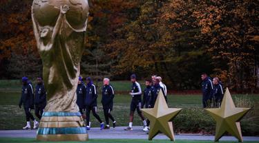 Para pemain timnas Prancis berjalan melewati relpika trofi Piala Dunia dan dua bintang saat bersiap berlatih di Clairefontaine-en-Yvelines (12/11). Prancis akan bertanding melawan Belanda di UEFA Nations League. (AFP Photo/Franck Fife)