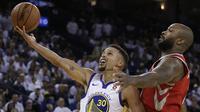 Aksi pebasket Warriors, Stephen Curry (kiri) melakukan tembakan lays up saat diadang pebasket Houston Rockets, PJ Tucker pada laga perdana NBA 2017 di Oracle Arena, Oakland, (17/10/2017).  Rockets menang 122-121. (AP/Ben Margot)