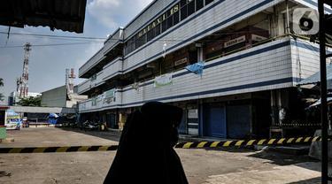Warga melintasi Pasar Pulogadung yang sedang ditutup sementara di Jakarta, Senin (29/6/2020). Perumda Pasar Jaya menutup sementara Pasar Pulogadung selama tiga hari hingga 27 Juni 2020 setelah ditemukannya satu orang pedagang positif Covid-19 berdasarkan hasil Swab Test (merdeka.com/Iqbal S Nugroho)