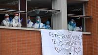 Petugas kesehatan bertepuk tangan untuk mengenang Esteban, perawat yang gugur karena virus corona COVID-19 di Rumah Sakit Severo Ochoa di Leganes, Spanyol, Jumat (10/4/2020). Hingga Minggu (12/4/2020) pagi, total kasus COVID-19 di Spanyol sebanyak 163.027. (Photo by PIERRE-PHILIPPE MARCOU/AFP)