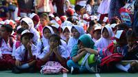 Murid-murid sekolah dasar duduk di halaman sekolah SDN 03, Pesanggrahan, Jakarta Selatan, Senin (16/7). Hari ini merupakan hari pertama masuk sekolah bagi para siswa dari jenjang TK hingga SMA untuk tahun ajaran 2018-2019. (Merdeka.com/Arie Basuki)