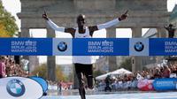 Pelari Kenya, Eliud Kipchoge tiba di garis finis Berlin Marathon ke-45 di Berlin, Jerman, Minggu (16/9). Kipchoge memangkas 1 menit 17 detik dari rekor dunia yang sebelumnya dipegang Dennis Kimetto di ajang lari yang sama. (AP Photo/Markus Schreiber)