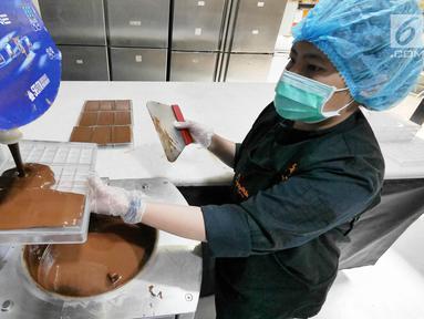 Pekerja memasukkan cokelat cair ke dalam alat cetak di toko Pipiltin Cocoa kawasan Barito, Jakarta, Kamis (13/9). Pipiltin Cocoa cukup banyak diburu oleh para atlet Asian Games 2018. (Liputan6.com/Herman Zakharia)