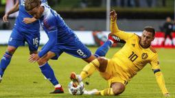 Penyerang Belgia, Eden Hazard, berebut bola dengan pemain Islandia, Birkir Bjarnason, pada laga UEFA Nations League di Stadion Laugardalsvollur, Selasa (11/9/2018). Belgia menang 3-0 atas Islandia. (AP/Brynjar Gunnarsson)