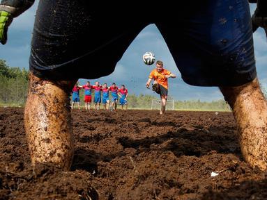 Seorang pemain sepak bola rawa melakukan tendangan penalti dalam turnamen sepak bola rawa di desa Pogy, 60 km (37 mil) dari St. Petersburg, Rusia pada 22 Juni 2019. Meski lumpur menghambat kecepatan atlet, olahraga yang berasal dari Finlandia ini digemari di beberapa negara. (AP/Dmitri Lovetsky)