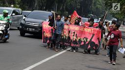 Sejumlah pemuda Papua berjalan kaki menuju kawasan depan Istana Negara, Jakarta, Kamis (2/8). Aksi ini untuk memperingati 49 tahun penentuan pendapat rakyat (Pepera) 1969. (Liputan6.com/Helmi Fithriansyah)