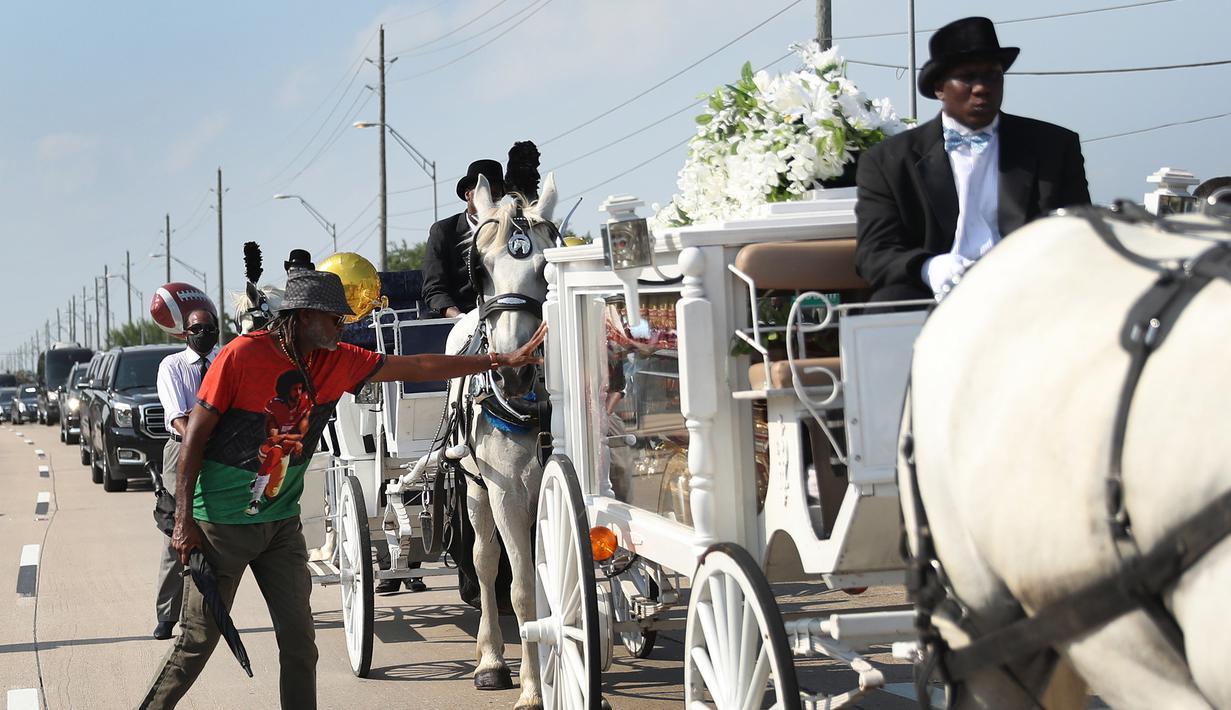 Seorang pria menyentuh kereta kuda yang membawa jenazah George Floyd saat menuju pemakaman Houston Memorial Gardens di Houston, Texas, Amerika Serikat, Selasa (9/6/2020). Floyd akan dimakamkan di samping makam ibunya, Larcenia Floyd. (Joe Raedle/etty Images/AFP)