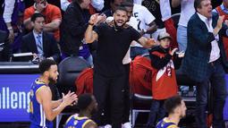 Penyanyi Rapper Drake bersorak saat menyaksikan pertandingan kelima Final NBA 2019 antara Golden State Warriors melawan Toronto Raptors di Scotiabank Arena, Toronto, Ontario (11/6/2019). Warriors mengalahkan Toronto Raptors dengan 106-105. (Nathan Denette/The Canadian Press via AP)