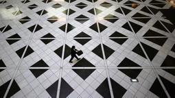 Seorang pria yang mengenakan masker untuk membantu mengekang penyebaran virus corona berjalan di sebuah gedung di Tokyo, Kamis, (27/8/2020). (AP Photo/Eugene Hoshiko)