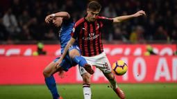 Striker AC Milan, Krzysztof Piatek, berebut bola dengan bek Empoli, Ismael Bennacer, pada laga Serie A di Stadion San Siro, Milan, Jumat (22/2). Milan menang 3-0 atas Empoli. (AFP/Marco Bertorello)