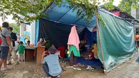Puluhan pengungsi di tenda darurat di depan Kantor Dinsos Sulbar, Selasa (19/01/2021). Selama empat hari di lokasi itu mereka mengaku sulit mengakses kebutuhan dasar; makanan, air, dan MCK. (Foto: Heri Susanto/ Liputan6.com).
