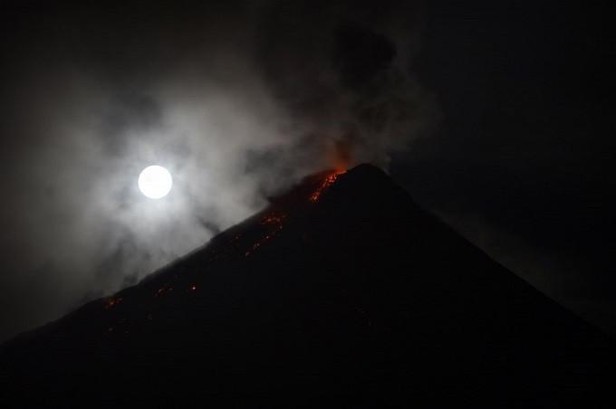 Super Blue Blood Moon dikaburkan oleh awan yang menerangi gunung berapi Mayon saat menebarkan abu di dekat Kota Legazpi, provinsi Albay, Filipina, 31 Januari 2018. (AFP PHOTO/TED ALJIBE)
