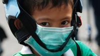 Seorang anak laki-laki mengenakan masker saat dijemput orang tuanya di Bangkok (30/1). Kementerian Kesehatan Thailand memberi peringatan kepada warga dan turis untuk menghindari kegiatan di ruang terbuka dan mengenakan masker. (AP Photo/Sakchai Lalit)