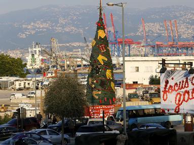 Pakaian dan peralatan milik petugas pemadam kebakaran yang tewas dalam ledakan di Pelabuhan Beirut diletakkan pada sebuah pohon Natal di Beirut, Lebanon (20/12/2020). Pohon Natal ini didirikan pada Minggu (20/12) di dekat Pelabuhan Beirut. (Xinhua/Bilal Jawich)