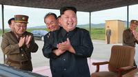 Pemimpin Korea Utara, Kim Jong-Un merayakan uji coba peluncuran rudal balistik Hwasong-12 di lokasi yang tidak diketahui pada foto yang dirilis Sabtu (16/9). Kim Jong-Un bersumpah akan menyempurnakan kekuatan nuklir negaranya. (KCNA/KNS via AP)
