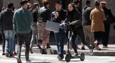 Seorang wanita menyebrang jalanan mengendarai skuter bermotor di San Francisco (17/4). San Francisco menghentikan operasi perusahaan yang menyewakan skuter bermotor. (AP/Jeff Chiu)