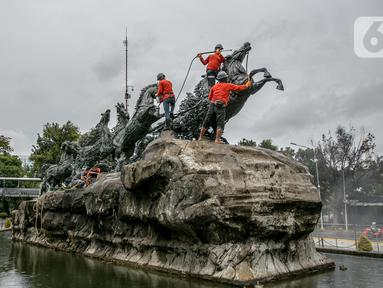 Aktivitas pembersihan dan perawatan patung kuda Arjuna Wijaya di Jalan Medan Merdeka, Jakarta, Rabu (27/1/2021). Patung yang dibangun sejak 1987 karya pematung Nyoman Nuarta tersebut dibersihkan dan ditata kembali untuk memperindah kota. (Liputan6.com/Faizal Fanani)