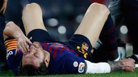 Megabintang Barcelona, Lionel Messi meringis kesakitan setelah mendarat tak sempurna saat terjatuh dalam lanjutan Liga Spanyol di Camp Nou, Minggu (21/10). Messi mengalami cedera patah tulang tangan saat berduel dengan pemain Sevilla. (AP/Manu Fernandez)