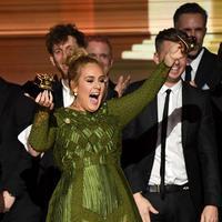 Pemborong lima piala dan pembuka acara di Grammy Awards 2017, Adele malah mematahkan piala di atas panggung lantaran merasa tidak pantas menerima penghargaan itu serta membaginya kepada Beyonce. (AFP/Bintang.com)