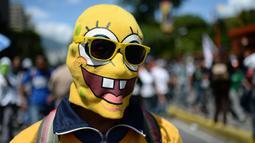 Seorang demonstran menggunakan penutup wajah berkarakter SpongeBob saat unjuk rasa menuntut Presiden Venezuela, Nicolas Maduro mundur di Caracas, Venezuela, (6/7). (AP Photo / Federico Parra)