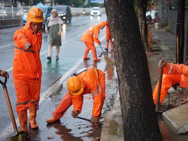 Petugas PPSU membersihkan saluran air yang tersumbat di Jalan Mampang Prapatan Raya, Jakarta, Rabu (11/12/2019). Hal tersebut dilakukan guna mengurangi genangan air yang terjadi di sejumlah sudut Ibukota setiap kali hujan deras mengguyur Jakarta. (Liputan6.com/Immanuel Antonius)