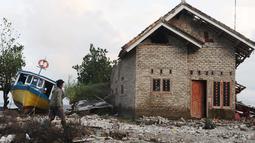 Seorang warga mengecek kondisi rumah yang ditinggalkan di dusun Regahan Lada, Pulau Sebesi, Lampung, Senin (31/12). Banyak warga dusun ini yang bertahan di lokasi pascatsunami yang melanda Selat Sunda pada 22 Desember lalu. (Liputan6.com/Herman Zakharia)