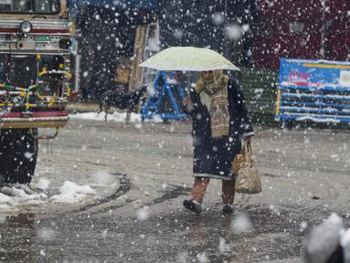 Seorang wanita Kashmir berjalan saat salju turun di Srinagar, Kashmir yang dikuasai India (15/1/2020). Selama dua hari terakhir wilayah Himalaya telah menyaksikan hujan salju lebat yang mengakibatkan serangkaian longsoran dan tanah longsor. (AP Photo/Dar Yasin)